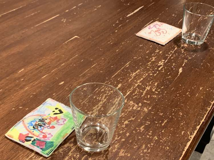 View of the washed off table with two transparent water glasses spaced a seat apart with the name tag laid out by each one.