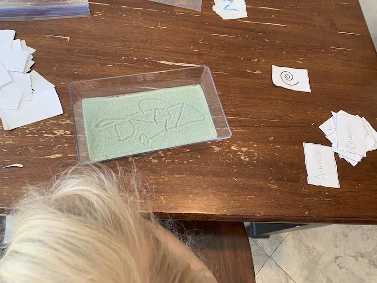 Closeup of Zoey's tray, and top of her head. The tray shows her doodle consisting of lines, a circle, a triangle, and two squares all interconnected. The sight words and shapes are on either side of her tray (hers to the right and Ada's to the left).