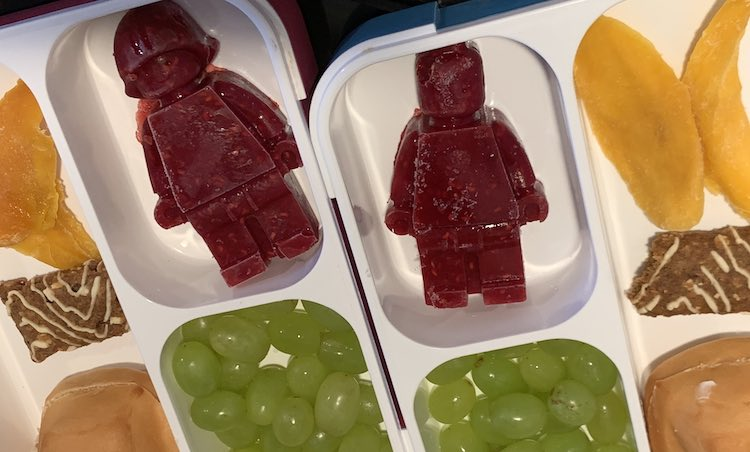 Closeup of the bento boxes side by side. Both LEGO® people (female and male) are shown. The other pockets, slightly cut off, show the dried mango slices, halved Z-bar, bun with cream cheese, and grapes.