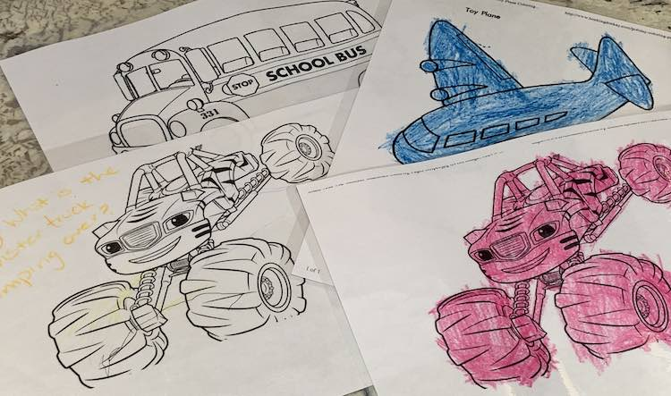 Four laminated images are spread out on the counter. Two shows a monster truck, one a blue airplane, and the last a school bus.