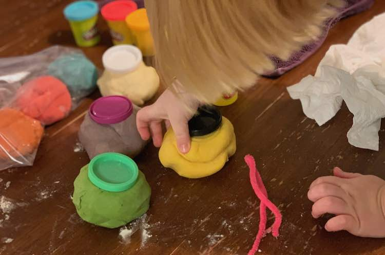 Image shows Ada placing a black lid on the yellow mound of playdough. The green, purple, and white beside it match up. You can see the first colors filled behind and their excess amounts in a clear bag beside it.