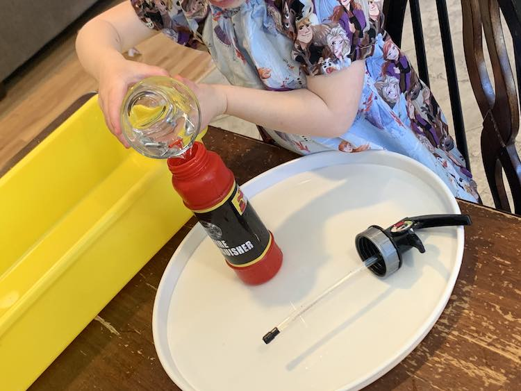 Closeup of Zoey pouring water into the opened fire extinguisher toy standing on a plastic tray. The lid lays beside it and the yellow sensory bin lays behind it.