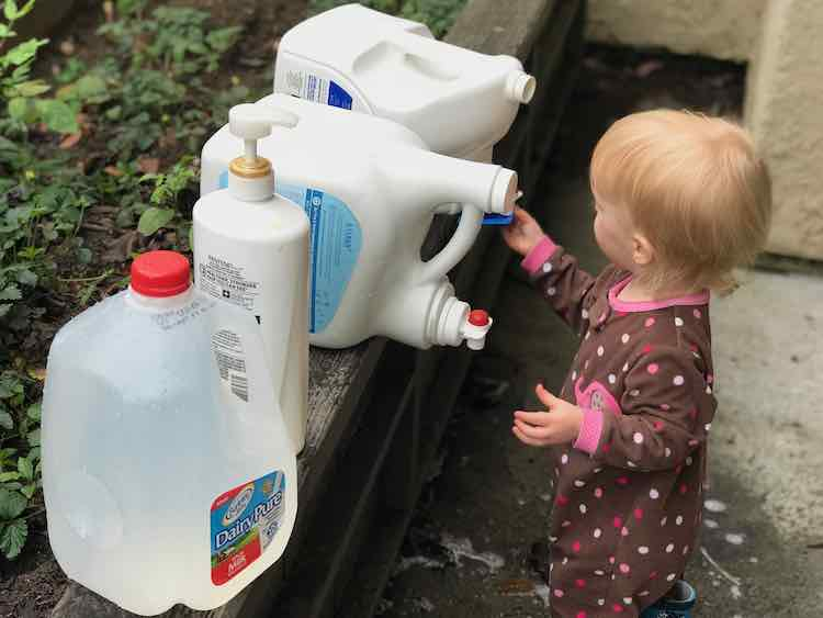 Zoey is shown attempting to get water out of the jug by holding up a mould against the spigot without trying to turn it on. Lined up next to the bottle is another detergent bottle, shampoo pump bottle, and a filled milk jug lined up going towards you.