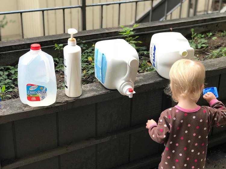 Zoey standing in front of the row of filled bottles playing happily.
