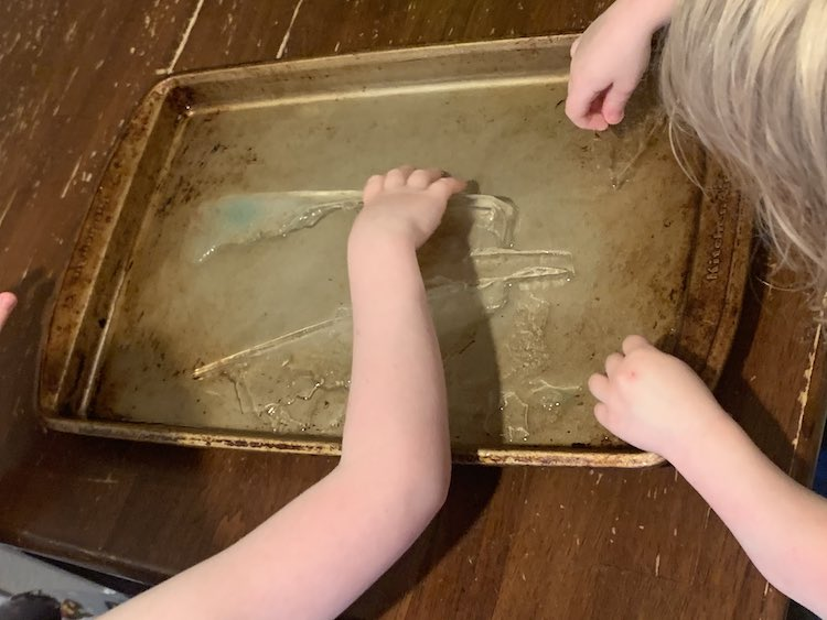 Overview of the cookie sheet on the kitchen table. There's ice frozen to it and the kids are leaned over it picking the ice off to play with.
