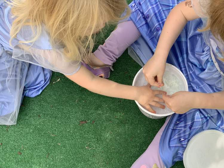 Ada sitting on the fake grass with the container of ice between her legs. She's reaching into the container to play with the frozen bubbles. Zoey crouches beside her and is reaching into the container.