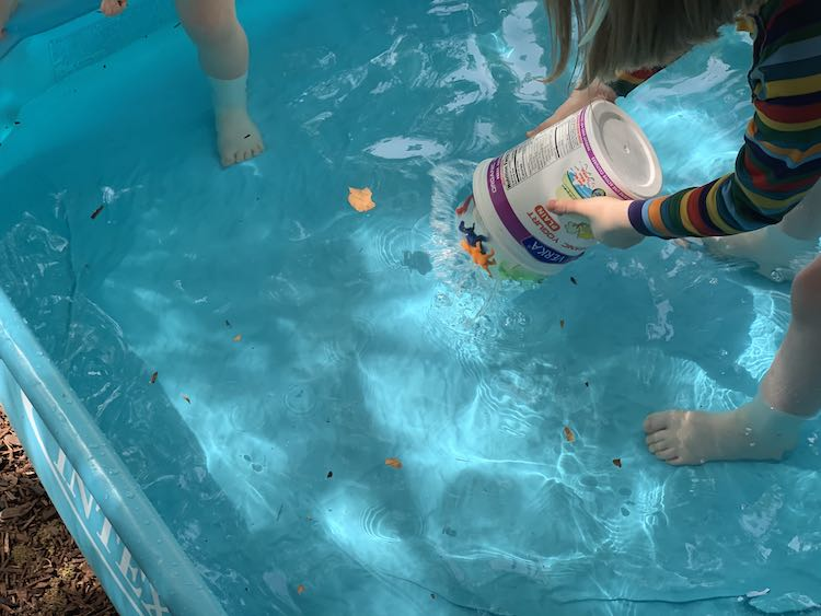 Zoey's foot off to the side shows her getting into the pool. To the right Ada is crouched over holding the upside down container dropping the ice into the pool.
