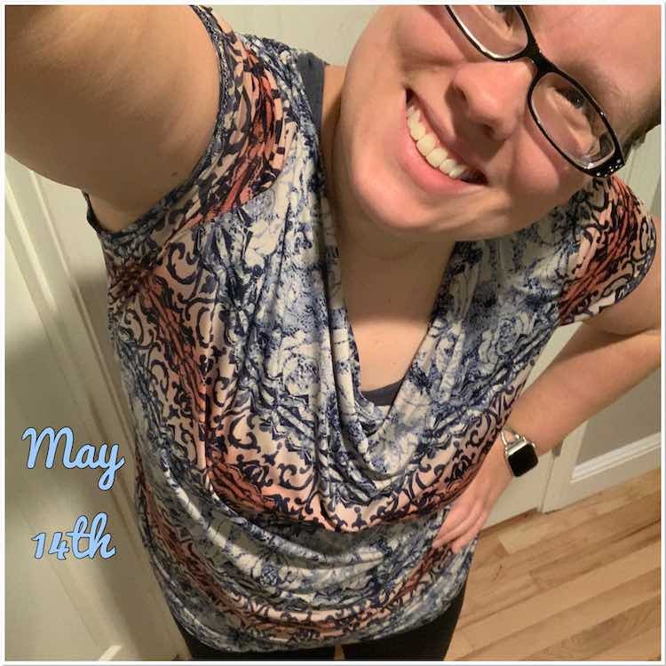 Selfie view with my head tilted and my other hand on my waist. Shirt drapes down in the neckline showing my matching blue brazi underneath. The fabric is a slinky ITY with horizontal blue, white, and pink patterns going across which showcases the draping.