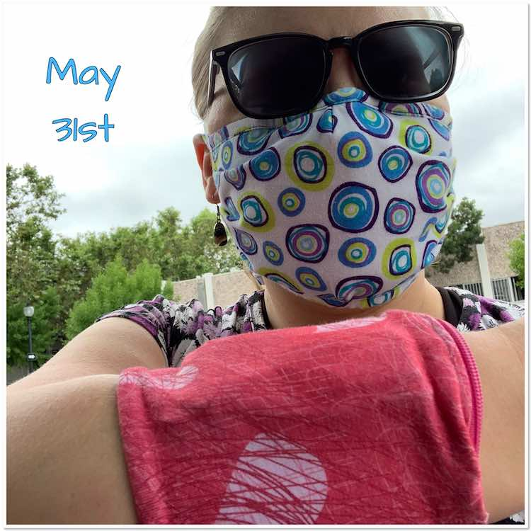 Selfie outside rather than most of the other indoor ones. Here I'm wearing sunglasses, a mask, and a cuff on my visible arm. Behind it all you see a hint of a previously work purple flowered Dynamite shirt. The mask is white with colored circles and you can see the bias tape along the top is made of the same fabric. The cuff is pink with scribbled hearts in white and lighter and darker pink.