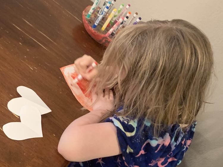 Side of Ada sitting at the table coloring a paper heart red. Behind her is holder with all the markers and in front of her are two more paper hearts.