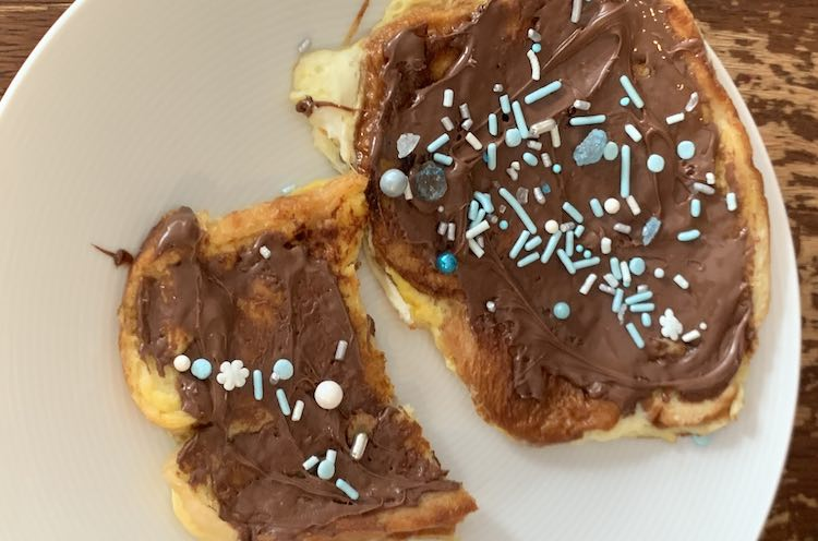 Overview of white plate with one and a half french toast slices decorated in brown Nutella and colorful blue and white 'ice' sprinkles from Walmart.