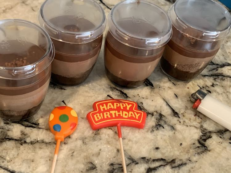 Closeup of four of the chocolate mousse from Costco. They beside each other with distinct layers in a glass cup, each, and a plastic lid. In front are two candles (one orange balloon and one Happy Birthday one) with a white lighter going off photo to the right.