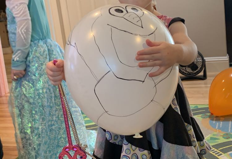 Closeup of the Olaf balloon in Zoey's arms, while she holds two wands, with Ada wearing an Elsa dress behind her.