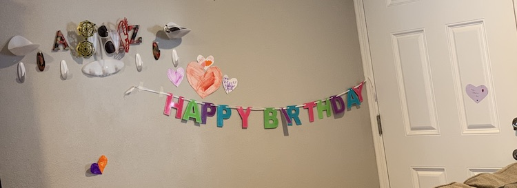 Wall with a multicolored sparkly Happy Birthday banner. There are six colored paper hearts around it and above it all, to the side, are the command hooks we use for the kids' jackets.