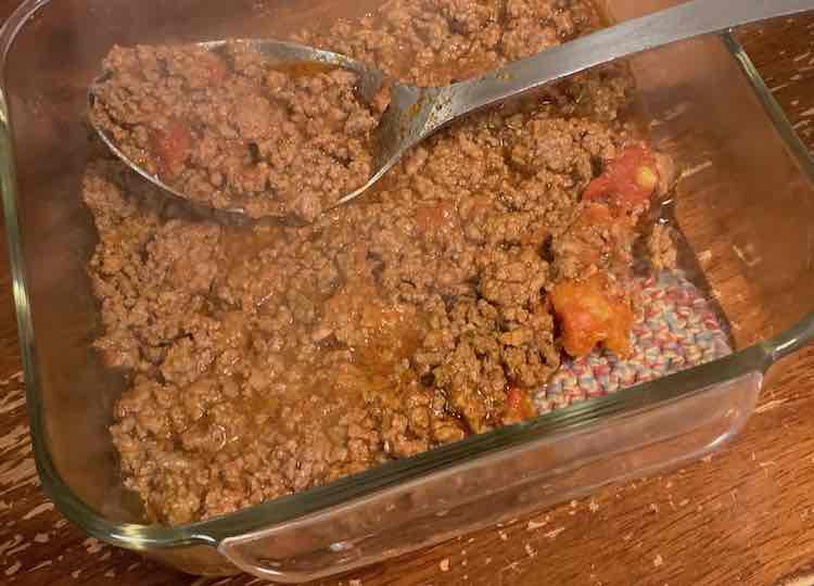 A square clear glass casserole dish sitting on a crocheted trivet. Meat sauce, including diced tomatoes, have been partially spread across the bottom. A metal spoon with meat sauce in it rests in the casserole dish.