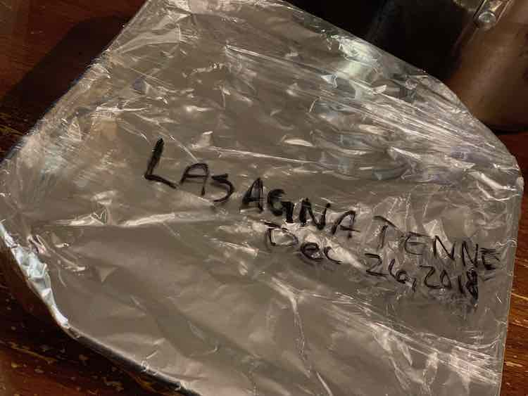 "View from above with the casserole dish top wrapped in tinfoil and then, partially, with plastic wrap. On the top of the plastic wrap it was written, in black, ""LASAGNA PENNE/Dec 26, 2018""."