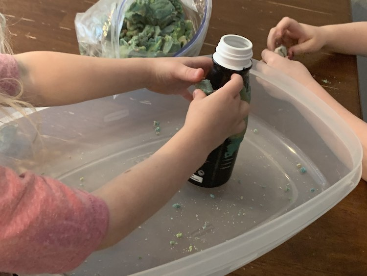Image shows the bottle held by Zoey within a large container bottom as she presses a piece against the side. Ada is prepping a piece to put on after her and an opened bag of playdough sits behind.