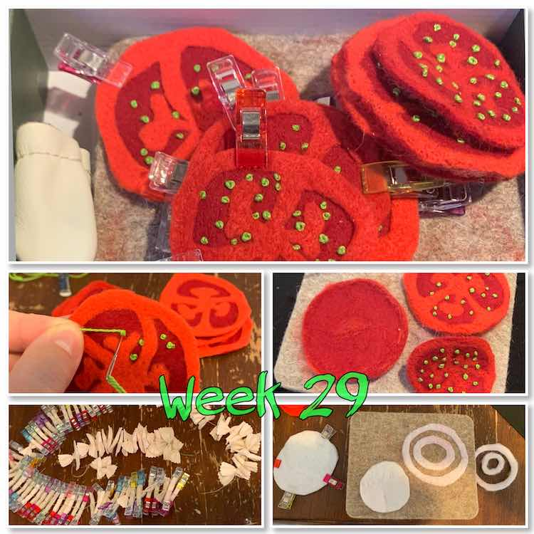 "Image is a collage of five photos with a green overlay centered near the bottom saying ""week 29"". The top image is of clipped together slices of tomatoes laid out over a felting wool board with a thumb cozy by it. The bottom four images are in a grid two by two. The top left image is of my making a green felt knot inside the tomato while the right image shows two tomato tops and one red bottom showing where the needle had poked through. The bottom two images don't contain felt tomatoes. Instead the left image shows a batch of felt pasta clipped and sewn while the right image shows felt onion rings being made."