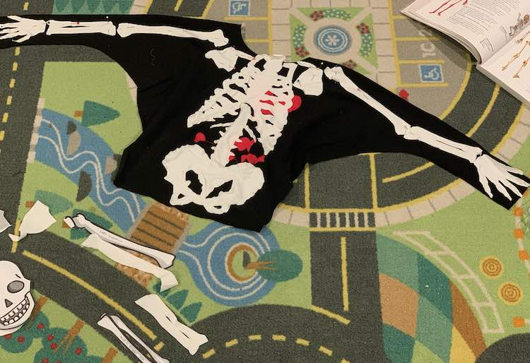 Image shows the car mat with the front of the shirt laid out on it. All the center bones, candy, and heart are sewn on while the arm, and related, bones are pinned on. Below you can see the extra bone pieces that haven't been used and above it the opened body book with the bottom of the skeleton diagram showing.