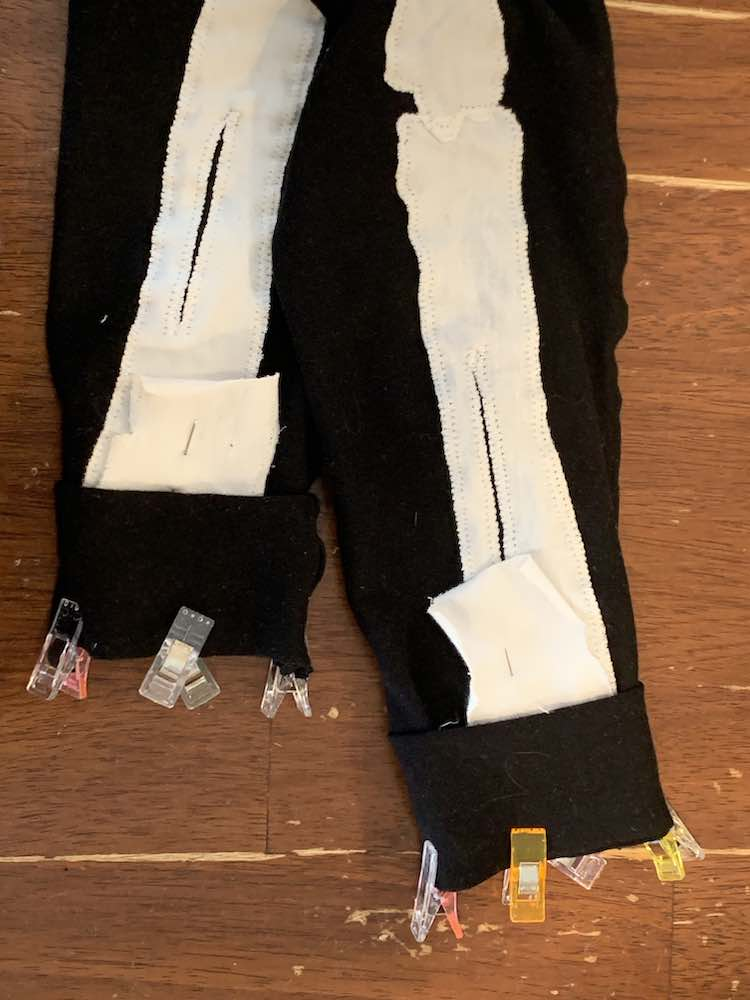 Image shows a closeup of the bottom of the pants with the white bones folded up and pinned in place. Hiding the bone fold is the cuff clipped in place.