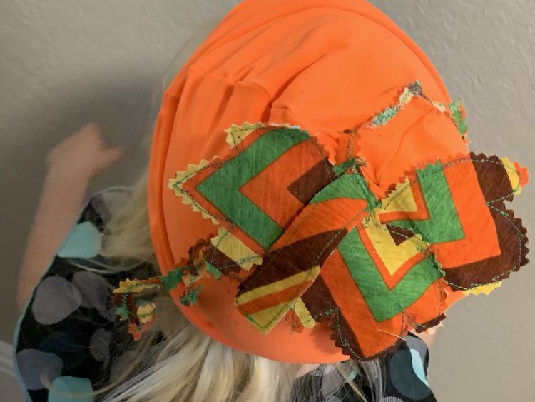 image shows the top of the beanie with the stem, leaves, and vines, mostly, drooping down. In the background is a white wall and the top of her body slightly blurred.