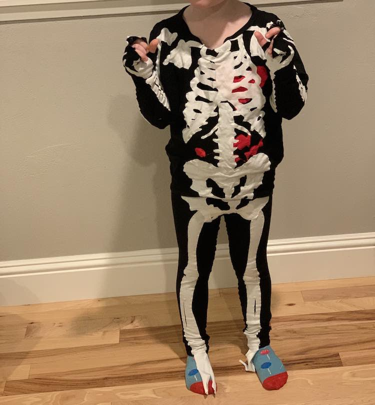 The image shows Ada from her neck down dressed as a skeleton with candy socks on to match the candy in her skeleton's stomach. Her arms are folded up as she wears the sleeves over her hands.