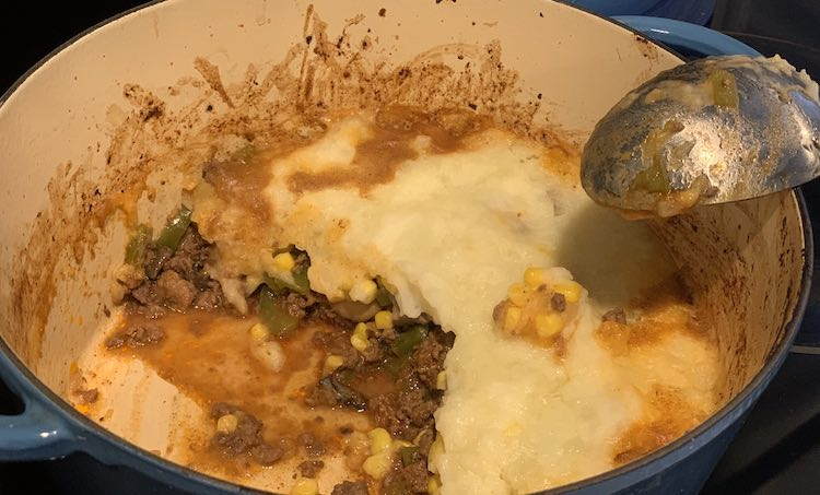 Photo taken from above looking down at a half filled dutch oven with shepard's pie. Along the edge you can see the ground beef mixture, with a dot of yellow and green, spilling out from the white topped section. A serving spoon sits leaned up against the pot edge.