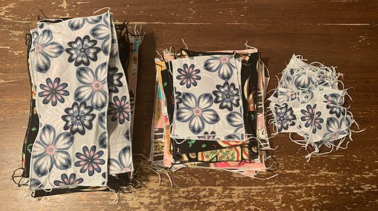 There are three piles on the table and the photo is take from above looking down on the piles. Each is topped with the grey flowered fabric though you can see the other two fabrics peaking out on the two left piles. The leftmost pile consists of large rectangular napkins, the center pile are smaller square napkins, and the rightmost pile are small single-layered face cloths.