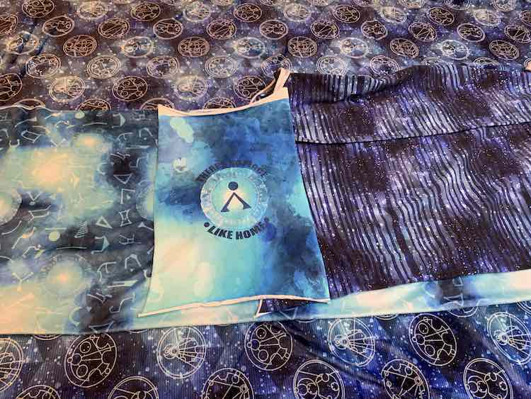 Most of the fabric laid out in one photo. The blanket topper is missing in this picture but the rest are showing. The background is the double plush Gallifreyan coordinate while the mink portals fabric lays across the center of the image. In the center of that lays the Stargate home cotton spandex panel with the striped cotton spandex beside it.