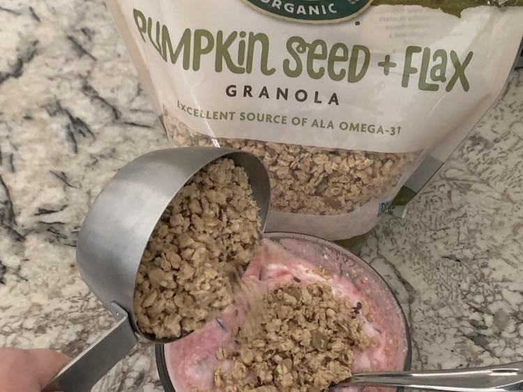 Image shows a glass circular container with mixed cherry and yogurt inside it. The yogurt is at the bottom of the photo with a bag of Pumpkin Seed + Flax Granola sitting behind it. There's a metal measuring cup with granola over top of the yogurt and it's tilted so the granola is pouring onto the yogurt.