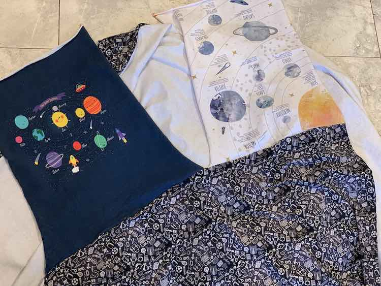 Image shows the coordinating black doodle fabric, along the bottom, with the two panels connected at the top. The panel on the left, navy blue with planets, if right side up while the panel on the right, white with a yellow sun surrounded by planets and descriptions, is upside down. The panels are only connected on the one side and not on any other side.