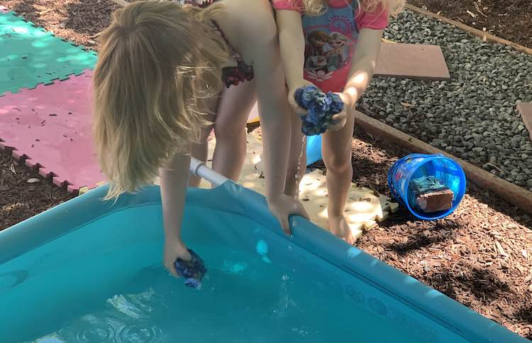 Both kids are standing behind the small pool. Ada is slightly in front and has one hand on the side of the pool as she bends over to soak the water balloon in her other hand. Zoey is slightly behind her and is squeezing her balloon out over the pool.