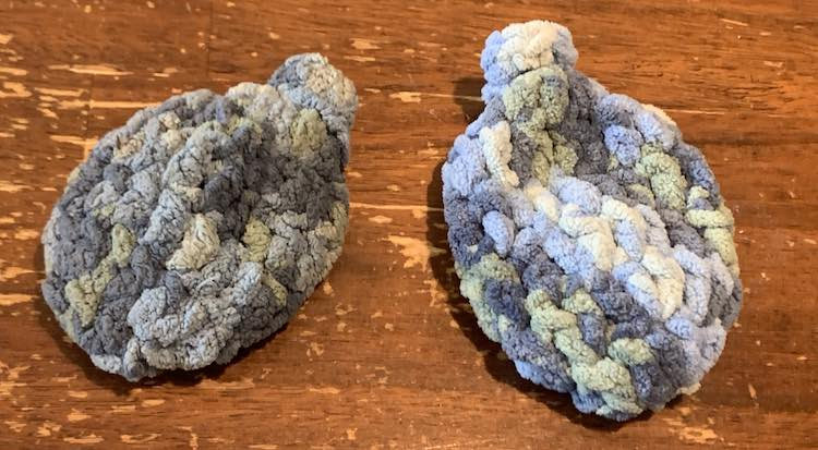 View shows two crocheted blue water balloons. The one on the left is dirty and shriveled looking while the one on the right is clean, dried, and puffy.