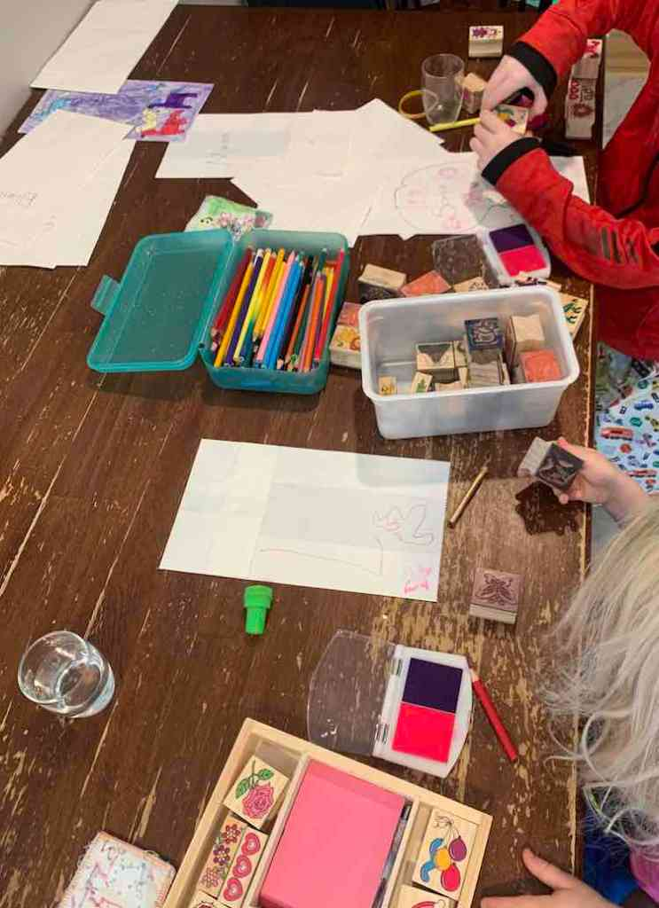 Over view of the girls sitting at the table decorating white paper bags. There's a container of pencil crayons between them and a bunch of stamps scattered around.