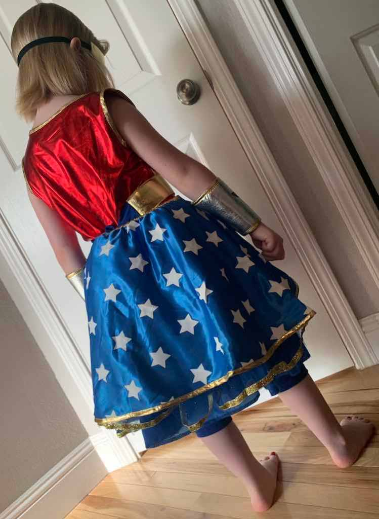 View of the back of the outfit. The blue leggings are, again, poking out from below the skirt and the skirt overlay hides the skirt itself, from the back.