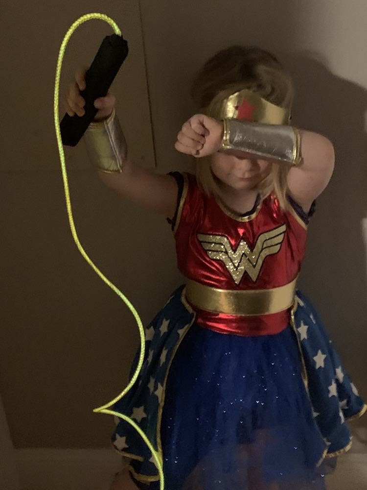 Image from above of Ada, as Wonder Woman, holding up the glowing lasso of truth, while blocking her face from attacks.