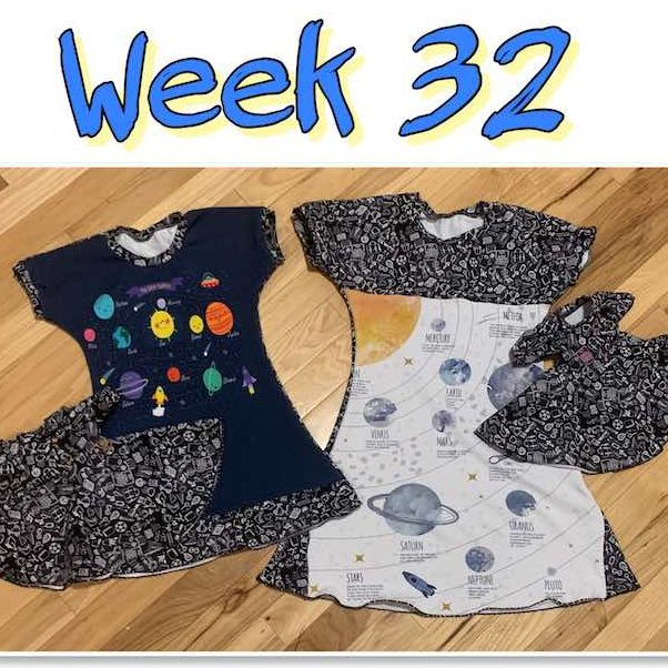 "Image is a large title ""Week 32"" over a single framed photo showing two dresses side by side with small doll dresses overlapped. Teh larger dress has a white panel with planets and labels on it while the smaller one has a blue panel with cartoony planets and a sun. Both dresses are bordered in a black fabric with school-related doodles on it. The doll dresses use the school doodles fabric with the odd one colored in so they can be told apart."