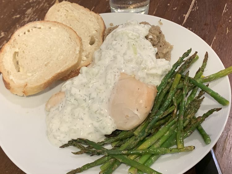 Image shows a plate with two slices of bread, quinoa and chicken coated in tzatziki, and a pile of asparagus.