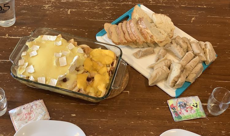 Photo was taken from above looking down at the table. On the left is the cheesy apple pie while the white blue tipped plastic cutting board sits beside it with two types of sliced bread. At the bottom of the image you can see the edge of two plates, two name tags, and two glasses.