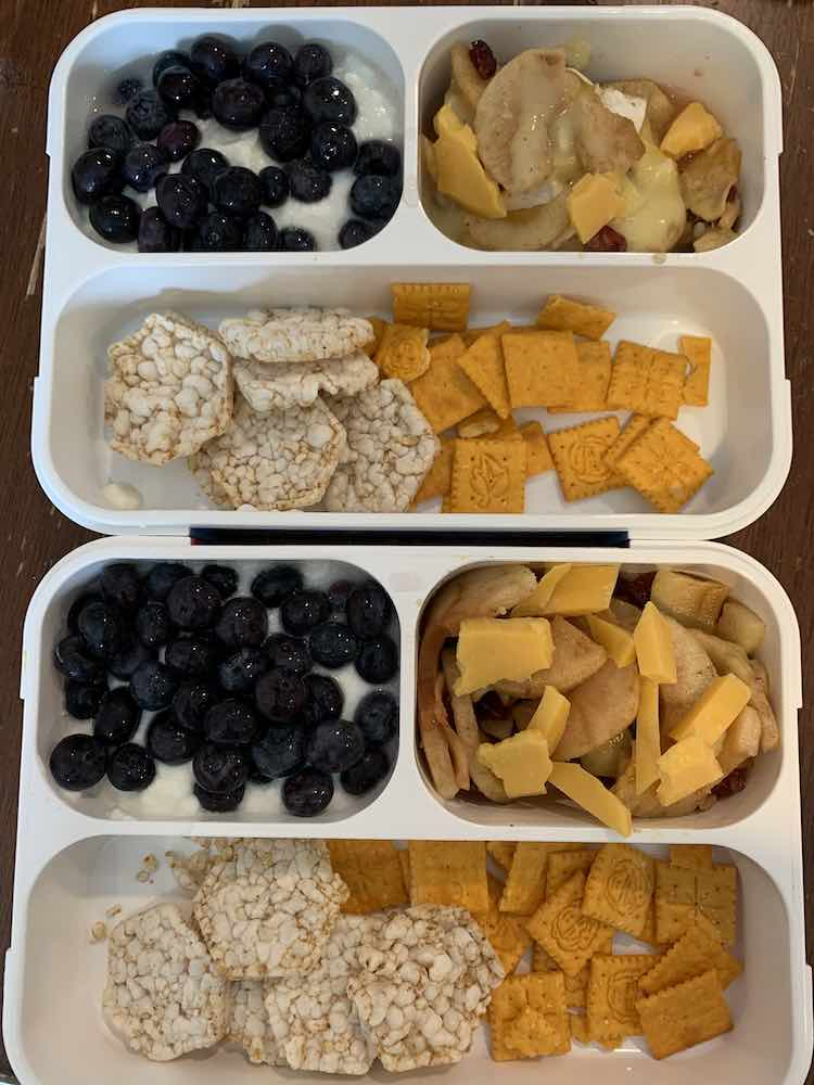 Image is taken from above showing two lunch boxes, appearing to be above and below each other, with similar contents. The only difference is one lunchbox has melted brie apples while the other one has a more plain looking apple filling.