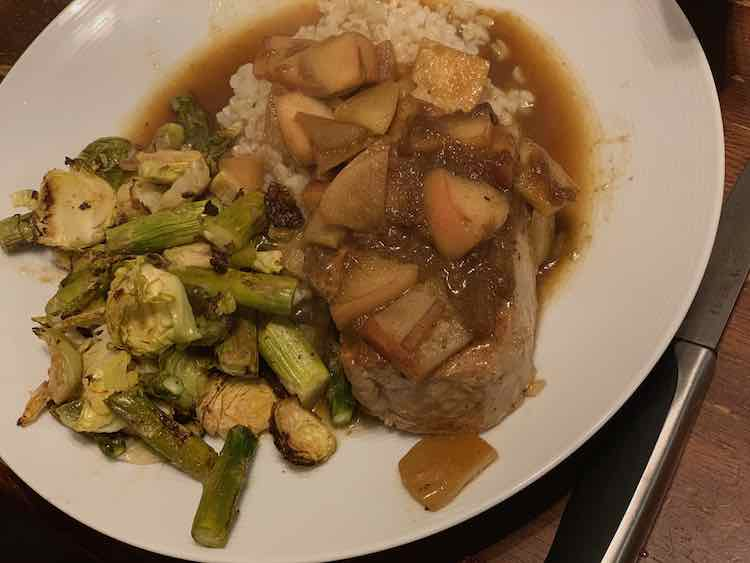 Image shows a white plate with a steak knife off to the side. On the plate is a pile of roasted diced Brussel sprouts and asparagus. Beside it is a pile of rice topped with a pork chop and apple topping. Around the food you can see the apple butter sauce.