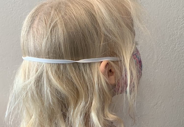View of the back and side of Zoey's head while she's wearing a mask with elastic going around her head. The lower elastic is hidden under her hair but the top elastic band goes over her ears and around the back of her head.