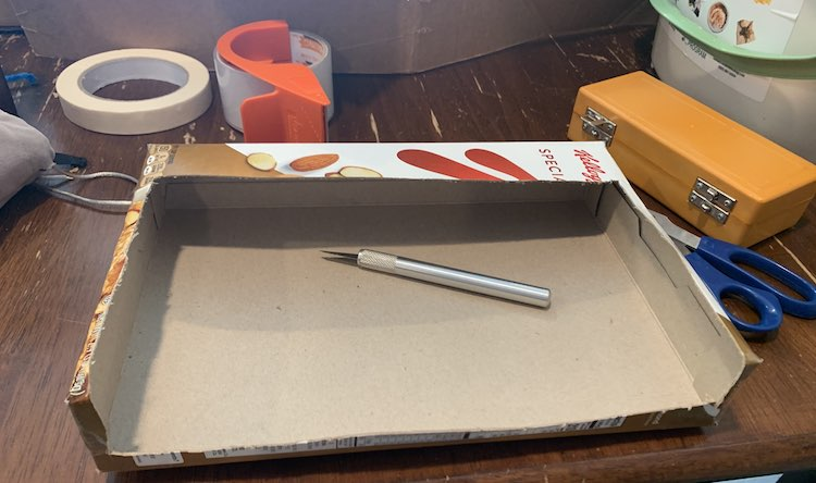 Image shows the box on it's side with most of the top and front cut away. There's a large stripe of box in the top back, a smaller section at the bottom front, and a smaller lip along the sides. The silver X-Acto knife sits in the opened box and the rest of the tools sit scattered around the box.