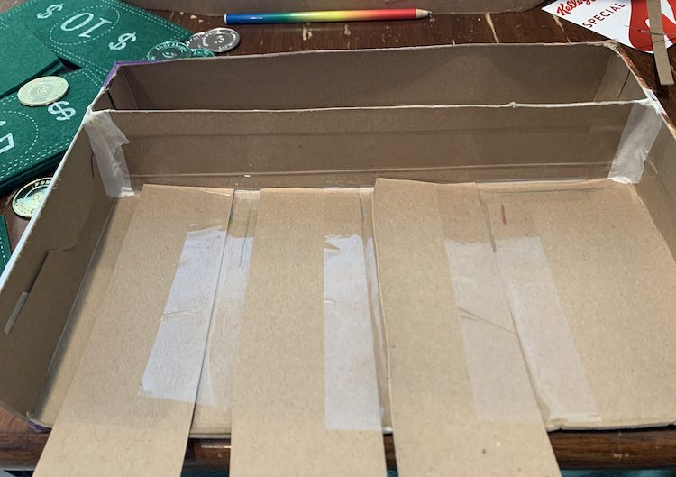 Image shows three dividers laid down at a ninety degree angle to the first divider. All have been taped down on the one side so each one overlaps the one next to it.