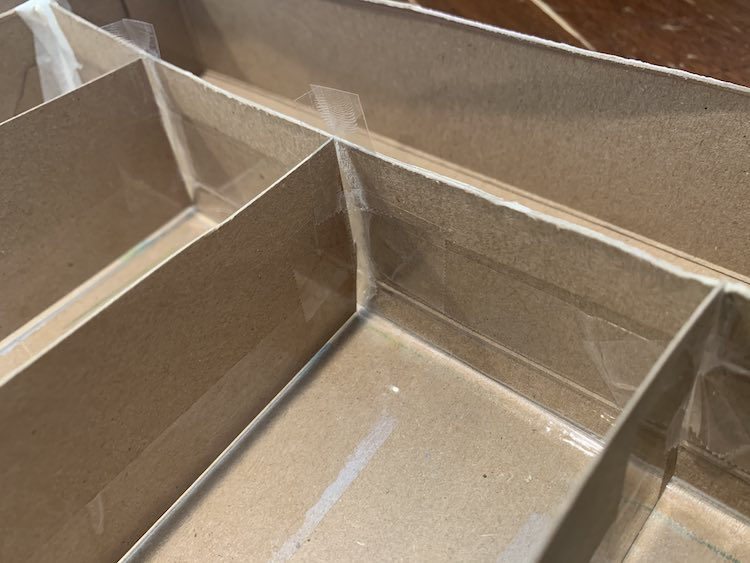 Image shows a closeup of the dividers' junction with tape facing upward about to be folded over to secure their place.