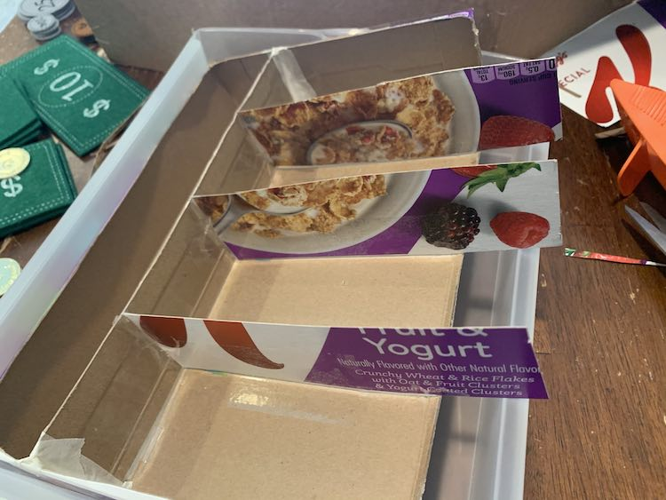 The cereal box organizer is tilted upwards in the plastic drawer as the three newly added dividers are too long to fit within the width of the drawer.