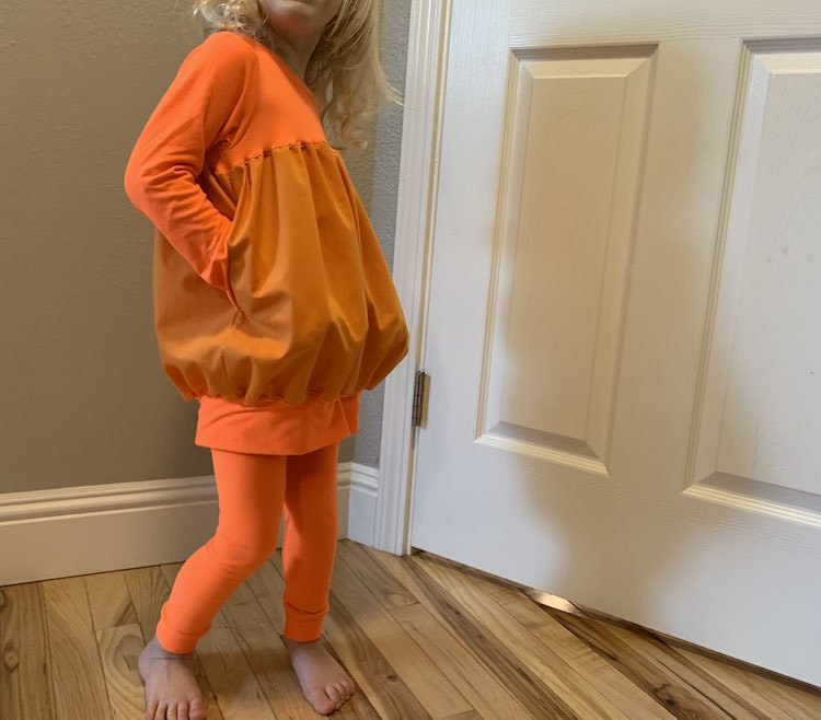 Zoey standing slightly turned with her hands in her pockets making the shirt look just a bit more pumpkin-esque.