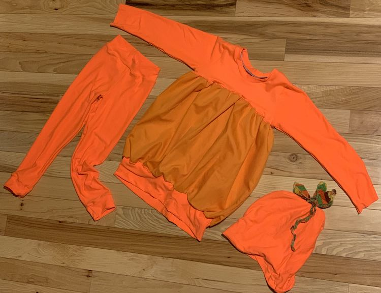 The image is taken from above showing a flat lay. The shirt is laid out in the center with the arms outstretched. Underneath the one arm are the leggings while the beanie is laid out under the other arm.