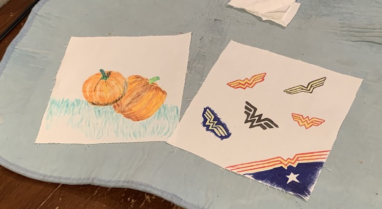 Image shows a blue ironing mat on the kitchen table with two rectangles laid out. In the background are a couple scraps of fabric, stacked, for the sides of the mask. The left rectangle shows two pumpkins with some grass below while the right one shows six Wonder Woman logos I copied from my internet search results.