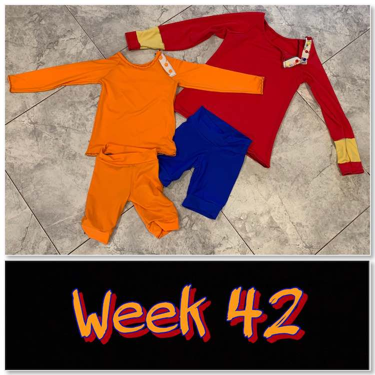"Image shows the finished swim garments laid out on the kitchen floor with a black rectangle below showing the words ""week 42"" in orange and red. The swim garments are composed of an orange rash guard,  orange shorts, red rash guard with yellow bands, and blue shirts."